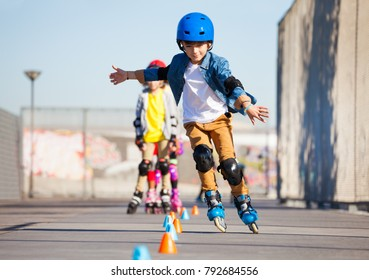 Young inline skater practicing forward slalom