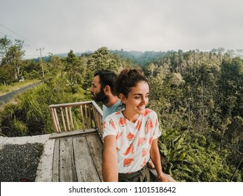Young and inlove couple in their honeymoon travling around Bali, Indonesia. Enjoying a day of sightseeing together discovering incredible jungle landscapes. Travel Photography.