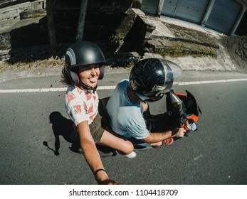 Young and inlove couple in their honeymoon travling around Bali, Indonesia with a motorbike. Enjoying a day of sightseeing together discovering incredible jungle landscapes. Travel Photography.