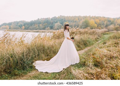 Young innocent bride posing outdoors. Cute charming girl with forest hills on background