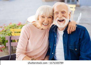 Young inside. Cheerful senior couple laughing and looking at camera