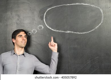 Young inspirated man standing nearly chalkboard background and pointing speech bubble