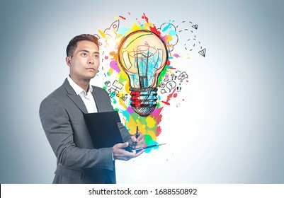 Young inspired Asian businessman writing on clipboard standing near grey wall with colorful business idea sketch drawn on it. Concept of creativity and brainstorming