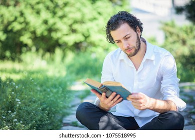 Young intellectual man reading a book in the park, enjoying his hobby all by himself, surrounded by tall green grass