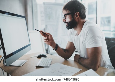 Young intelligent bearded man wearing eye glasses working at modern loft studio-office with desktop computer.Blurred background. Horizontal
