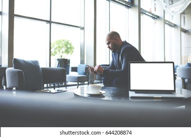 Young intelligent broker is searching for meeting needed information via mobile phone, while is sitting in coffee shop at the table with open net-book with empty copy space screen for your content
