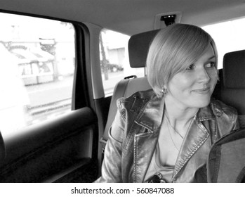 Young intelligent business woman sitting inside the car. She is glad, happy and smiling. Outside the window of the car - city street. Copy space to add text. Black & white.