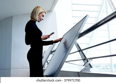 Young intelligent female phoning to partner via mobile phone while selecting information on high tech device, smart businesswoman holding cell telephone while exploring project on interactive monitor