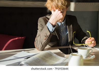 Young intelligent man rests of doing work or university project assignment at lunchtime in cafe. Tired male student takes off reading eyeglasses and rubs his eyes during coffee break after work