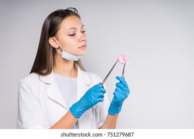 young intelligent woman doctor in white medical dressing gown is holding medical devices