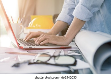 Young intelligent woman engineer hand typing on laptop keyboard near helmet and blueprint on modern glass table at home office. Model wearing vintage blue jean shirt.