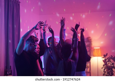 Young intercultural friends in smart casualwear raising arms while dancing together at home party in living-room illuminated with pink lighting
