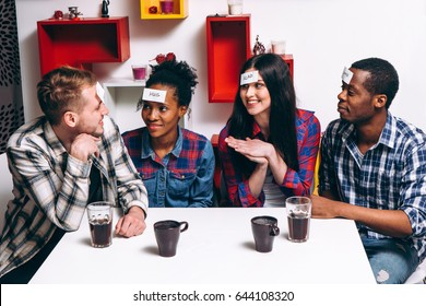 Young international company play funny game who I am. Four smiling people sit at the table with paper stickers. Home leisure, party, laugh, imagination concept.