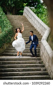 A young interracial couple (Indian man, Chinese woman) take wedding photos in Fort Canning Park, Singapore. They are running and jumping down stone stairs and laughing as they do so.
