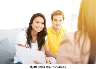 Young interracial couple meeting with consultant (or counselor, financial adviser, real estate agent etc.)