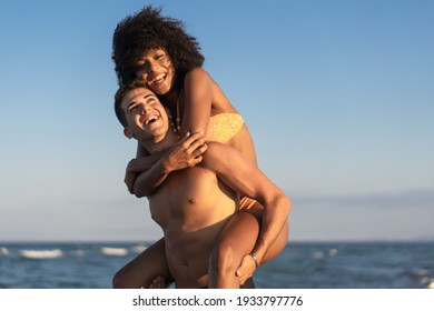 Young interracial couple in swimsuit having fun on the beach playing piggyback together in the summer.