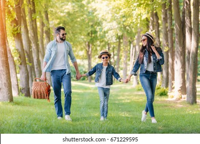 young interracial family with picnic basket spending time together in sunny forest
