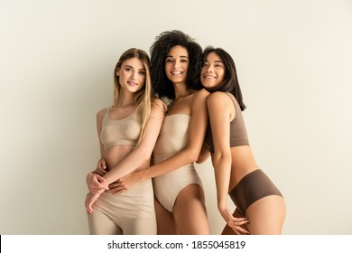 young interracial models in underwear smiling while posing isolated on white
