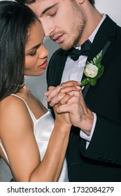 young interracial newlyweds holding hands while standing face to face with closed eyes on white background