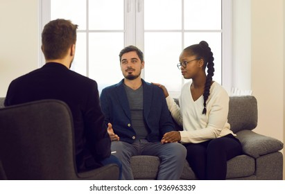 Young interracial spouses counseling at therapy session, talking about problems to man specialist at family consultation. Psychotherapist, financial consultant, lawyer or insurance agent meeting