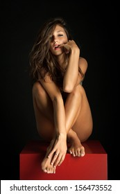 Young intimate woman beauty portrait against black background.