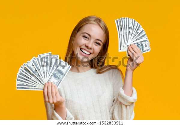 Young investor. Happy millennial girl holding lots of dollars on orange background with free space