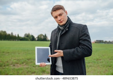 Young investor is presenting a content on tablet pc. Outdoor background.