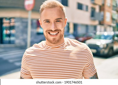 Young irish man smiling happy walking at street of city.