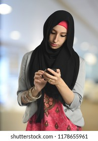 Young Islamic businesswoman messaging on the phone isolated on a white backgound