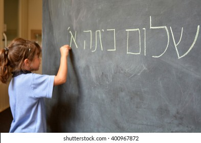 Young Israeli Jewish girl (Age 5-6) writes Hello First Grade greetings in Hebrew (Shalom Kita Alef) on chalkboard in Israeli primary school at the beginning of the school year. Real people.Copy space