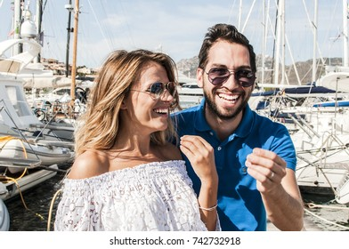 Young Italian couple gesturing in sunny harbor, selective focus