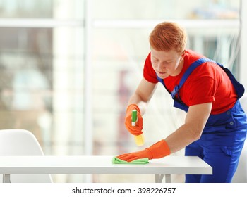 Young janitor with liquid detergent cleaning table in office