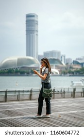 A young Japanese Asian tourist woman beholds and takes a photograph of the distinct Singapore cityscape from the vantage of Marina Bay Sands (MBS) in Singapore during the day.