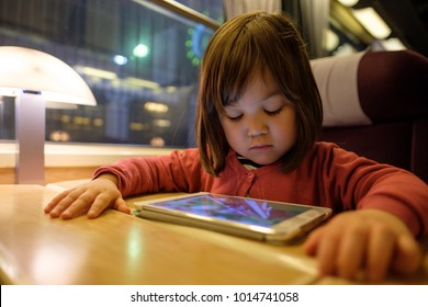 Young Japanese Child with her Tablet Computer in a high speed train.
