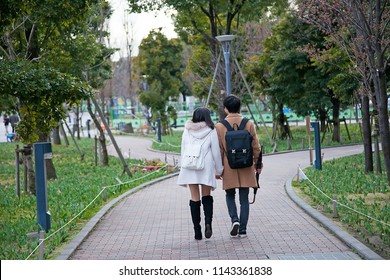 Young Japanese couple have a lovely moments,They are walking in the garden at odaiba island,This is a famous place in Tokyo,Japan