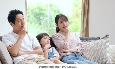 young japanese family thinking sitting on the sofa