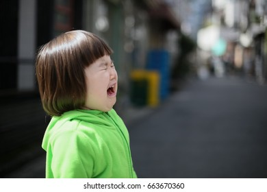 Young Japanese girl crying in the middle of the street.