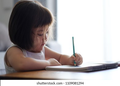Young Japanese girl drawing at home on a white notebook, sitting at a wooden desk, in a bright room.
