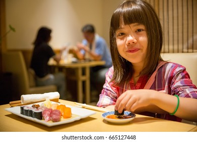 Young Japanese Girl eating Sushis in Hokkaido, Japan.