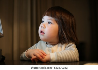 Young Japanese girl fascinated by a computer screen.