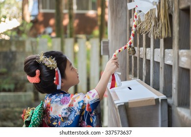A young Japanese girl in a kimono outdoors at a shrine ringing a bell