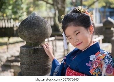 A young Japanese girl in a kimono outdoors at a shrine.