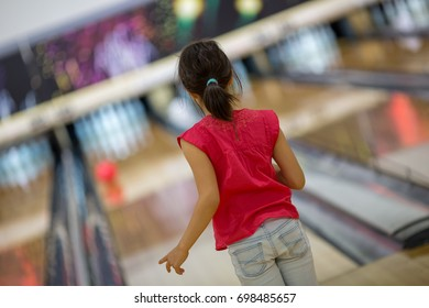 Young Japanese girl playing bowling in Tokyo.