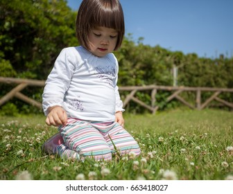 Young Japanese girl playing in the grass on a sunny day in a park in Japan.