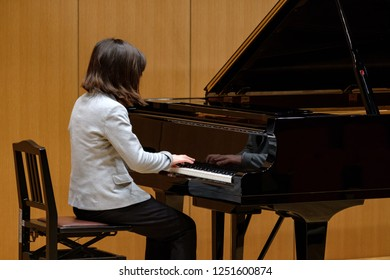 Young Japanese girl playing piano during a concert in Tokyo.