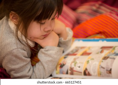 Young Japanese Girl reading a coming book on her bed.