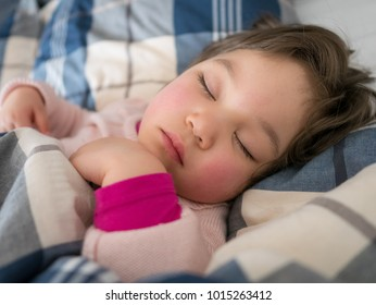 Young Japanese girl resting in a bed with a flu.
