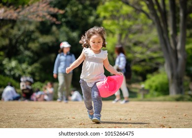 Young Japanese girl running while holding a pink hat. Her family on the background.