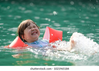 Young Japanese kid with red arm floats, having fun swimming in the sea during holidays: the cute girl is trying hard.