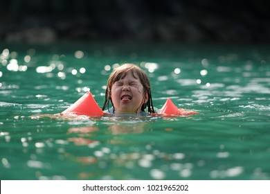 Young Japanese kid with red arm floats, having fun swimming in the sea during holidays: the cute girl does not like sea water.